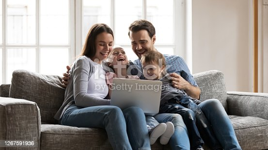 Happy bonding family sitting on cozy sofa, enjoying watching funny comedian movie on laptop at home. Overjoyed young family couple having fun, laughing at cartoons, spending weekend time together.