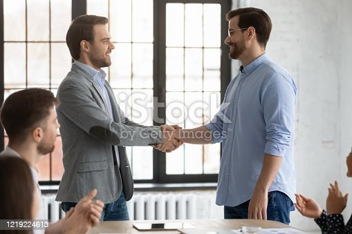 509032417 istock photo Happy boss shake hand greeting employee with promotion 1219224613