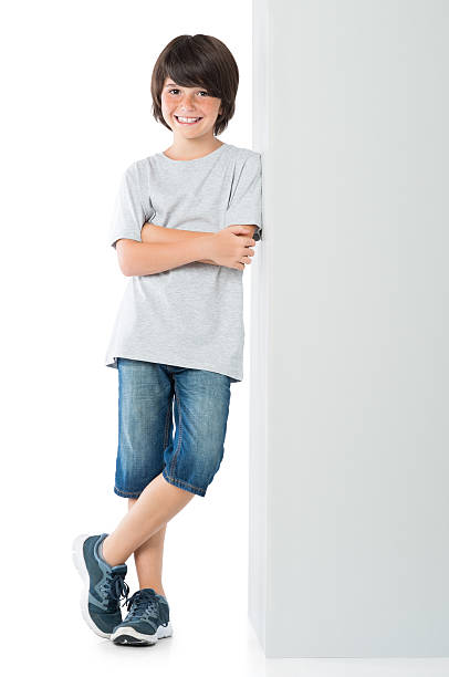 Happy boy against blank sign Smiling little boy posing against grey wall isolated on white background. Happy cute child standing against white background. Young boy leaning against a grey sign and looking at camera with arms crossed. leaning stock pictures, royalty-free photos & images