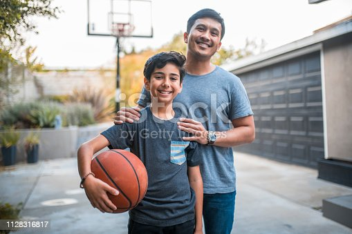 Portrait of happy boy and father standing at basketball court. Mid adult man and child are smiling in backyard. They are in casuals during weekend.