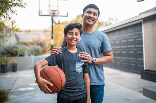 Happy boy and father standing at basketball court