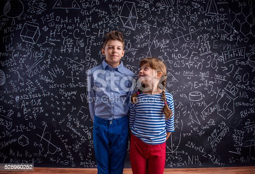 istock Happy boy and girl at school against big blackboard. 525960252