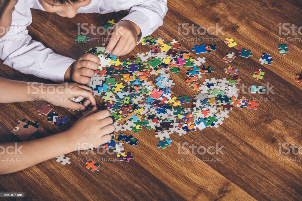Happy boy and girl collect puzzle lying on the floor - foto de stock