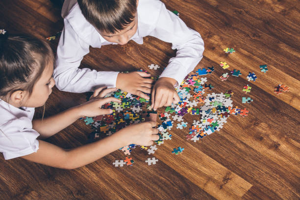 Happy boy and girl collect puzzle lying on the floor stock photo