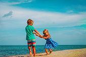 happy boy and girl dance at beach, kids enjoy vacation at sea
