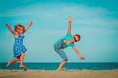 happy boy and girl enjoy playing at beach vacation, kids have fun at sea