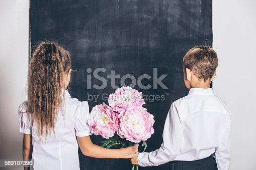 istock Happy boy and girl from elementary school with flowers 589107396