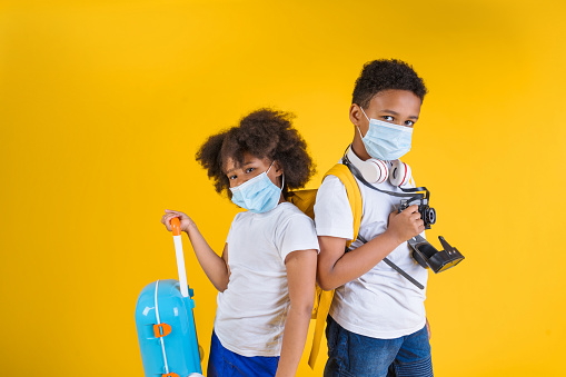Happy boy and girl in protective masks with backpack on yellow background