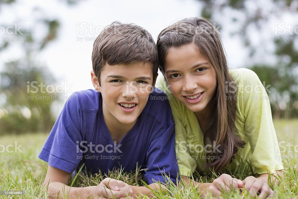 Happy Boy And Girl Lying On Grass royalty-free stock photo