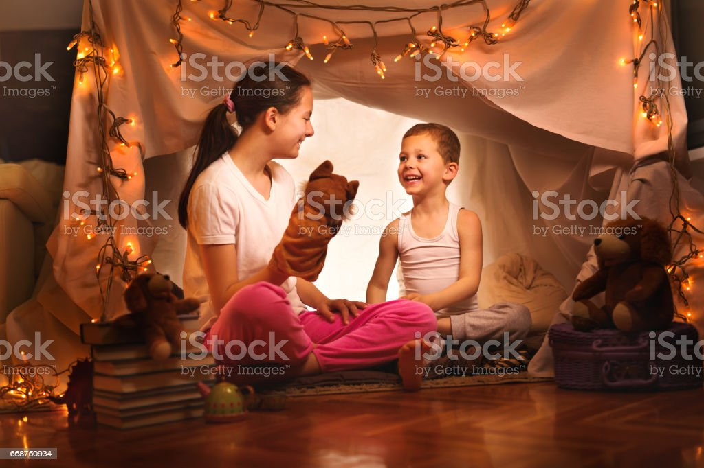 Happy boy and girl playing at home in a tent stock photo