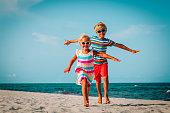 happy boy and girl run play at tropical beachhappy boy and girl run play at tropical beach