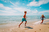 happy boy and girl running at beach, kids play with water at sea vacation