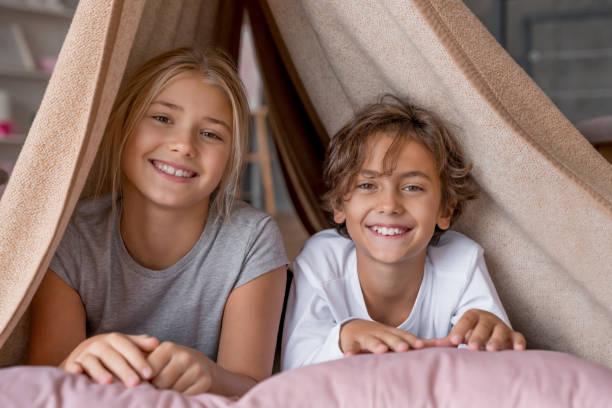 lycklig pojke och flicka sitter i fort från filtar och leende i kameran - fort bildbanksfoton och bilder