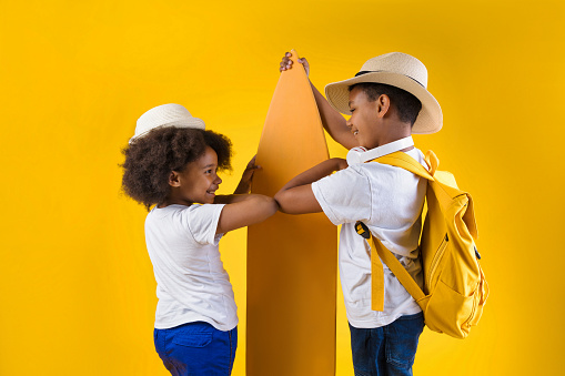 Happy boy and girl standing near surfboard on yellow background