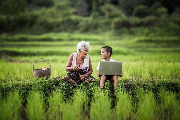 Happy boy and grandmother using laptop, asia thailand. stock photo
