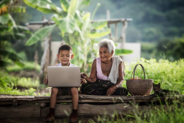 fröhlicher junge und großmutter mit laptop, bildung. - free online game stock-fotos und bilder
