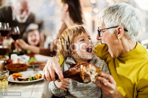 Happy boy and his grandmother having fun while about to eat turkey leg during family's lunch at home.