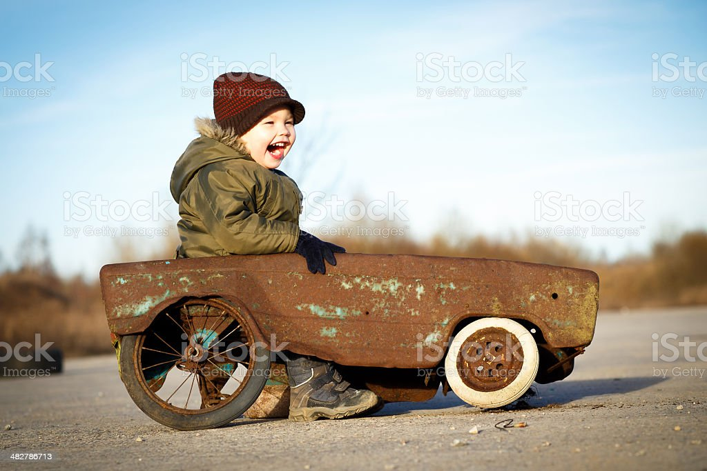 Happy boy and his toy car stock photo