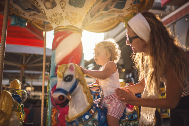 Happy Boy and Mother on Carousel stock photo