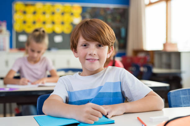 Happy boy at elementary school Portrait of happy child with freckles sitting at school desk in class room. Young boy smiling in class and looking at camera with his classmates in background. Pupil with red hair writing on notebook at elementary school. 8 9 years stock pictures, royalty-free photos & images