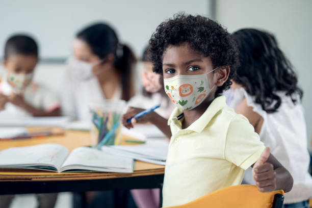 Happy boy at school wearing a facemask with thumbs up stock photo