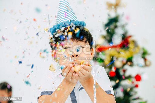 Happy boy celebrating party on a white background. Blows up glitter plastic paper flake.