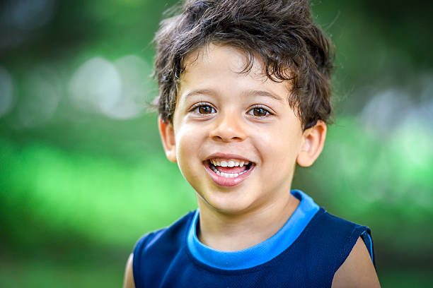 happy mulatto boy child is smiling enjoying adopted - bambini maschi foto e immagini stock