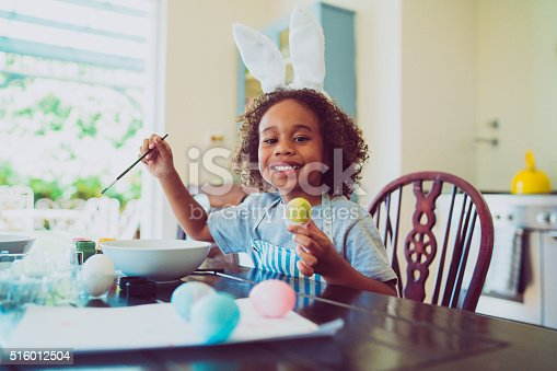 istock Happy boy coloring Easter egg at home 516012504
