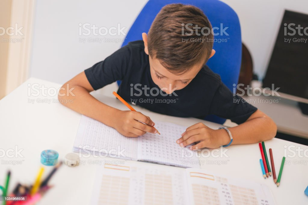 Happy boy doing his first homework stock photo