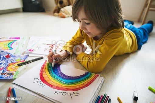 Happy boy drawing at home. Social distancing. Quarantine .Covid-19 crisis.