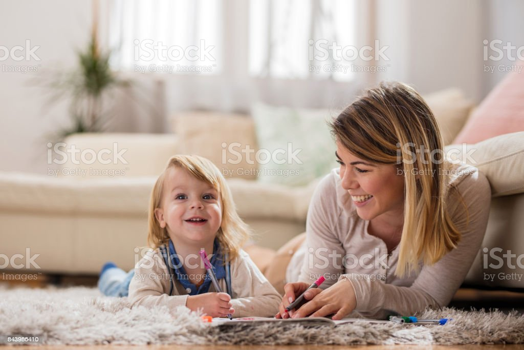 Happy boy drawing with his mother and enjoying a day at home. stock photo