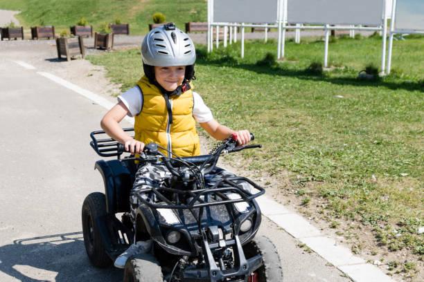 Happy boy driving quadbike on a road.
