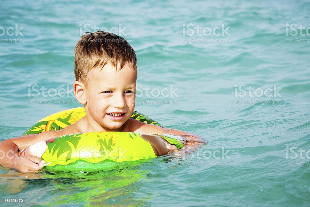 happy boy enjoying swimming in sea with rubber ring royalty-free stock photo