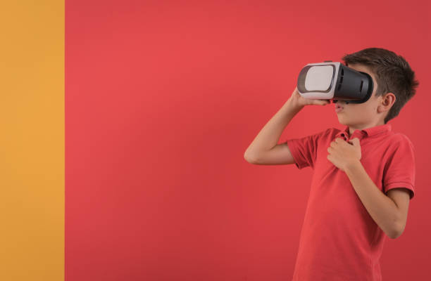 happy boy experiencing virtual reality in front of vibrant color - vr red background imagens e fotografias de stock
