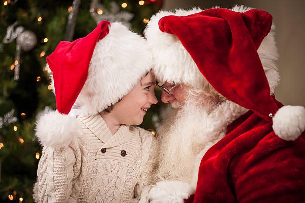 happy boy angesicht zu angesicht mit echten santa claus - sanft und sorgfältig stock-fotos und bilder