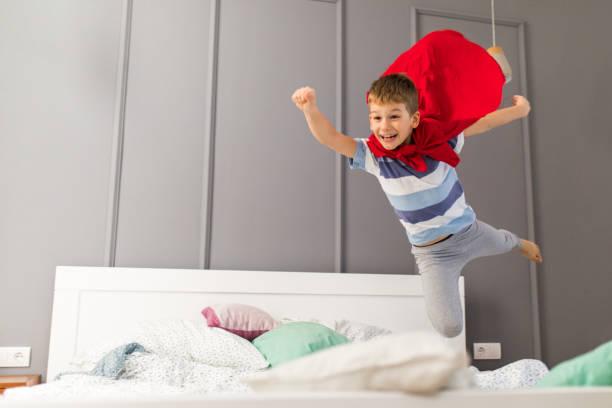 fröhlicher junge fliegen wie superman in einem schlafzimmer. - bett für jungs stock-fotos und bilder