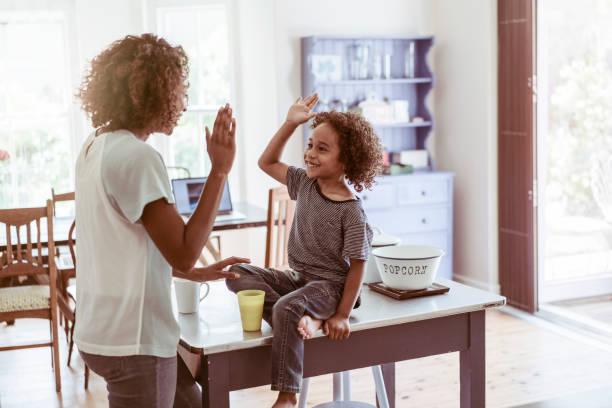 chico feliz dando de alto-cinco a la madre en casa - high five fotografías e imágenes de stock