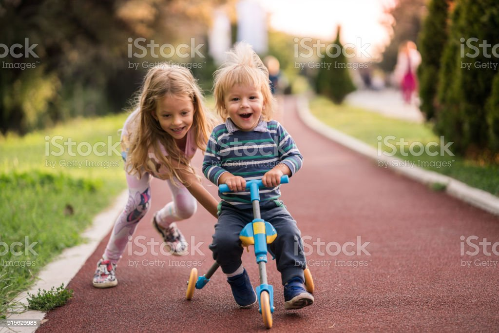Happy boy having fun on tricycle while his sister is pushing him. stock photo