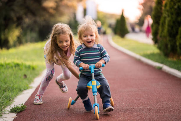 Happy boy having fun on tricycle while his sister is pushing him. Little girl helping her small brother with riding a tricycle in the park. brother stock pictures, royalty-free photos & images