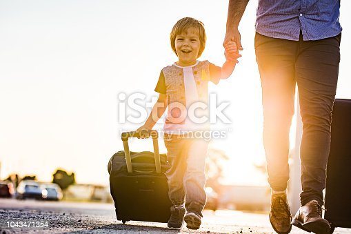 Happy little boy holding hands with his father while pulling suitcase at sunset.