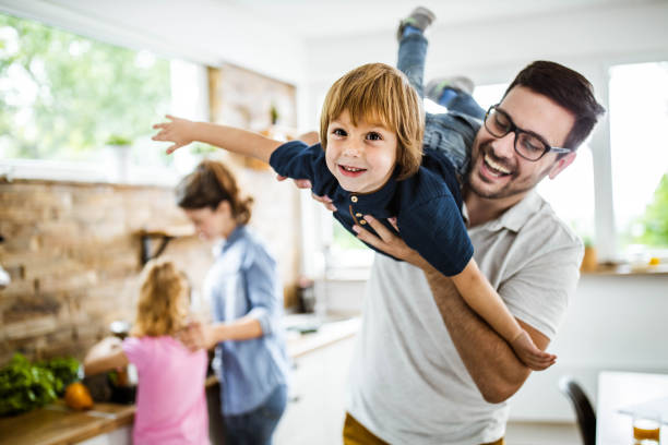 Happy boy having fun with his father in the kitchen. stock photo