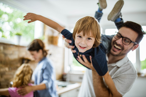 Happy little boy having fun with his father at home and looking at camera. There are people in the background.
