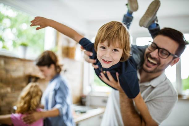 glücklicher junge mit seinem vater in der küche. - glücklichsein stock-fotos und bilder