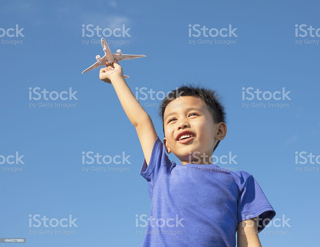 happy boy holding eine Flugzeug Spielzeug mit blauem Himmel – Foto