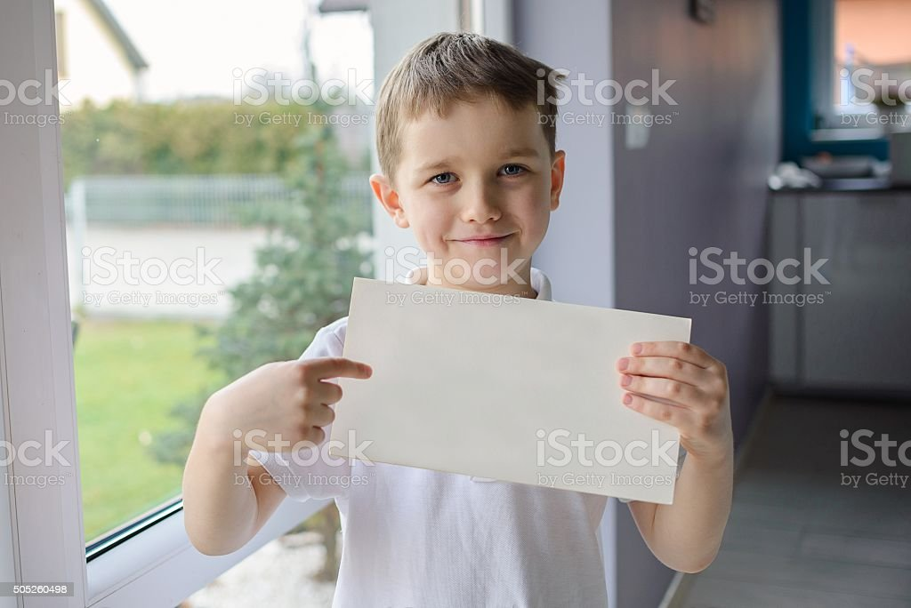 Happy boy holding an empty copyspace sheet of paper stock photo