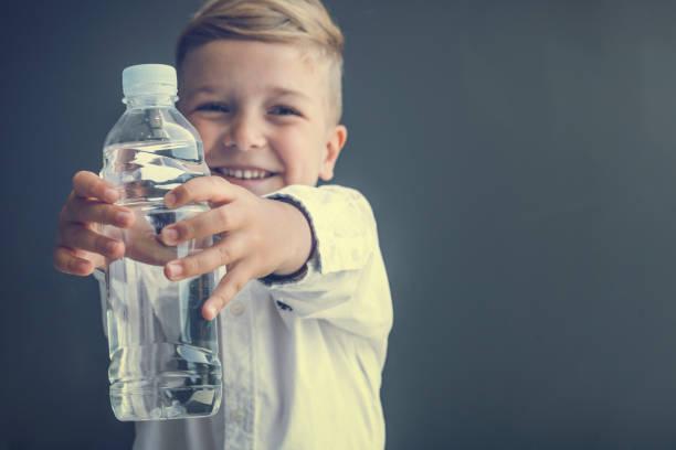 Happy boy holding bottle of water.