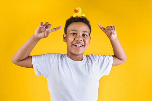 Happy boy holding rubber duck on the head on yellow background