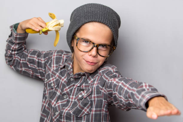 happy boy holds a banana, isolated over grey background.fast snack concept - nerd boy eating stock photos and pictures