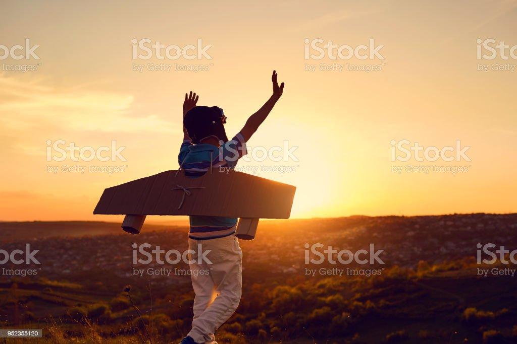Un niño feliz en un traje de superhéroe está jugando con un avión una - foto de stock