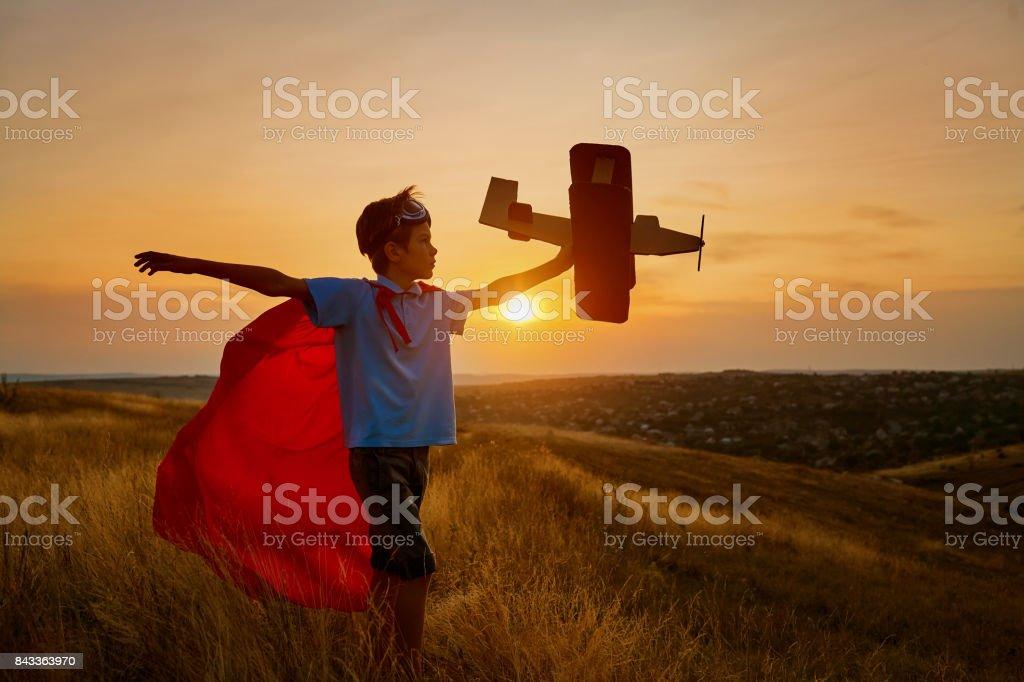 Un niño feliz en un traje de superhéroe está jugando con un avión. - foto de stock